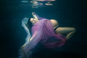 Pregnant woman under water.