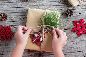 Girl's hands wrap christmas gift