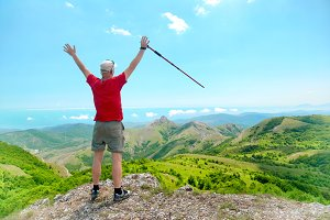 Young happy man with hiking stick