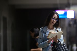 Young woman reads the book in subway