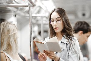 Girl reading a book on the subway in