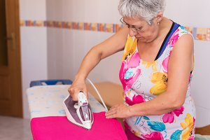 Senior woman ironing clothes