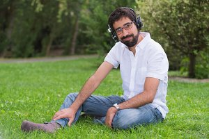 Young cheerful man listening music