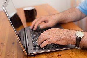 Close up senior man hands laptop