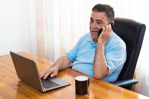 Cheerful Senior Man working laptop