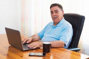 Cheerful Senior man working laptop