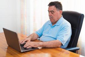 Senior man working on laptop.