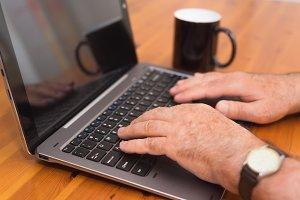 senior man hands working on laptop