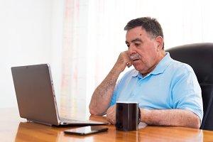 Senior man using laptop, doubtful