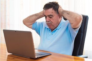 Surprised Senior working with laptop