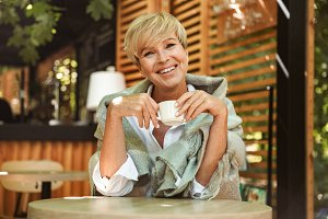 Cheerful mature woman wrapped in bla