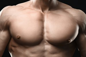 Perfect muscular male torso on black
