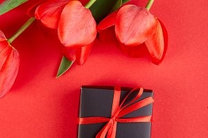 Black gift box with red ribbon near