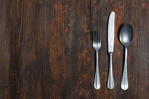 Old spoon and fork on brown wooden