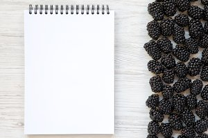 Blackberries with notepad on white