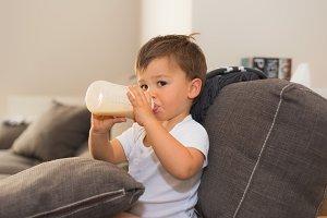 Adorable baby holding milk bottle