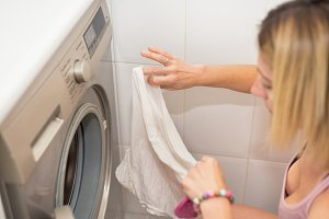 Young blonde woman doing laundry