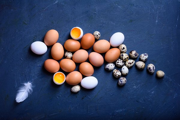 Chicken and quail eggs on a wooden