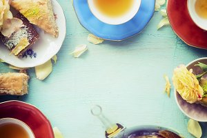 Cups of tea with cakes and tea pot