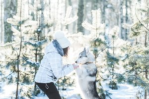 Girl playing with dog in winter