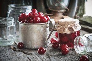 Mug of ripe cherries, jar of jam.