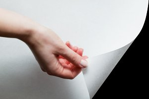 Hand pulling a bottom paper corner