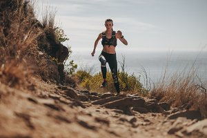 Fit woman running up the mountain