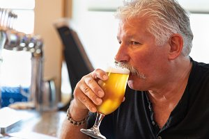 Man Tasting A Glass Of Beer