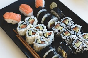 Homemade sushi rolls on black plate