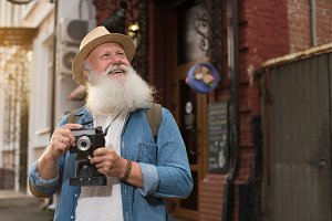 Happy smiling mature man with camera