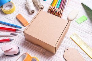 Cardboard box and stationery on wood