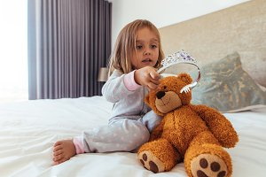Little girl playing with a teddy