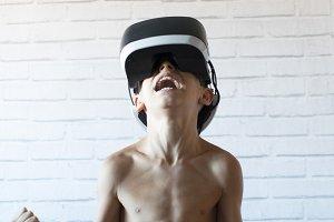 Little happy boy using VR glasses ov