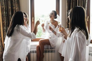 Laughing bride and bridesmaids drink