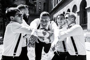 Groomsmen hold groom on their arms