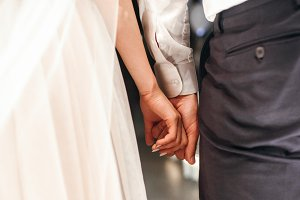 Groom holds bride's fingers tender