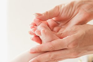 Hands of woman holds baby foot