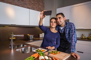 Couple in kitchen cooking and taking