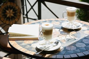Cup of coffee with book on table in