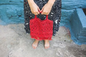Barefoot hipster girl with a red bag