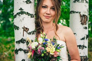Young bride near birches in the fore