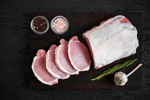 Pork chops on a black cutting board