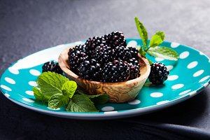 Ripe blackberries with leaves of min