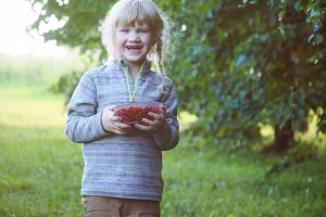 Baby with a bowl full of red currant
