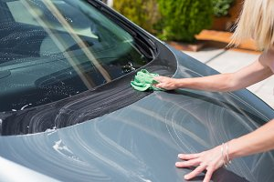 Young woman cleaning car