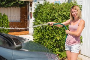 Young woman washing car with hose.