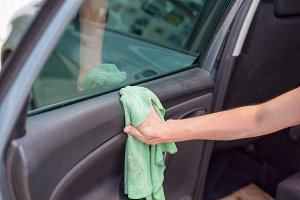 Young woman cleaning car interior