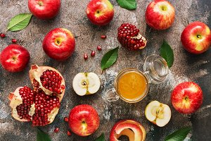 Apples, honey and pomegranate on a r