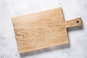 Empty wooden cutting board on white