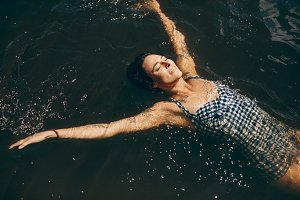 Woman in swimsuit swimming in lake